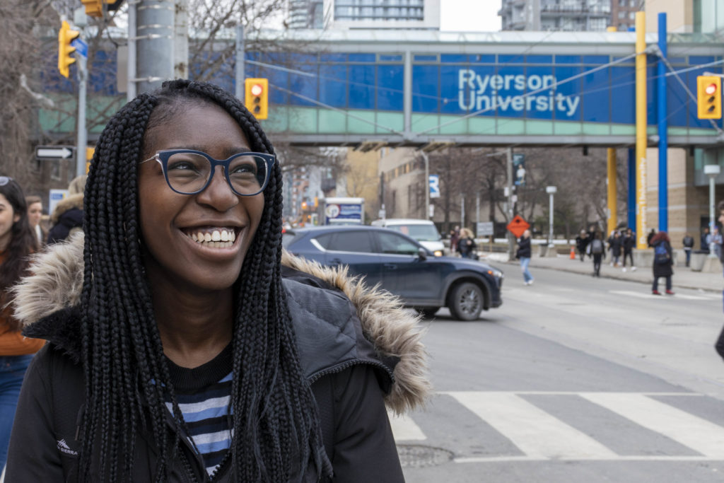 Folake smiling at an intersection located on the Ryerson University campus.